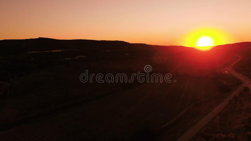 Red sunset. Shot. Red sunset sky with bright disk of sun partially hidden by mountains. Top view of traffic on rural. Red sunset. Red sunset sky with bright disk royalty free stock image