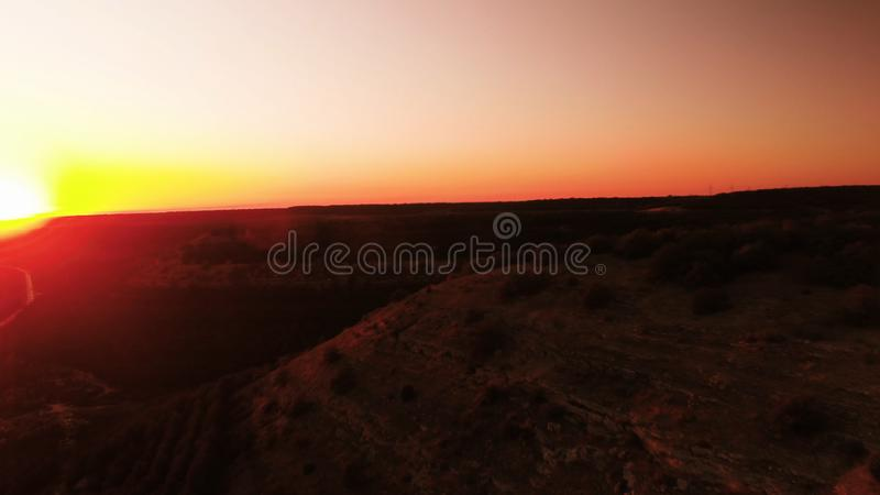 Red sunset. Shot. Red sunset sky with bright disk of sun partially hidden by mountains. Top view of traffic on rural. Red sunset. Red sunset sky with bright disk royalty free stock images