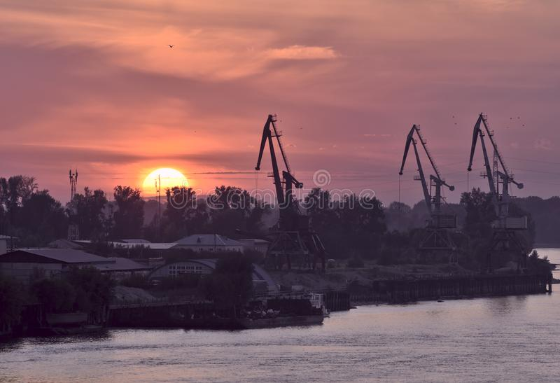 Red sunset with silhouettes of port cranes on the horizon royalty free stock images