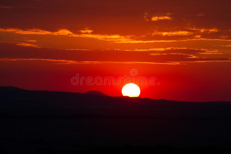 The red sunset sky with the sun and clouds stock photo