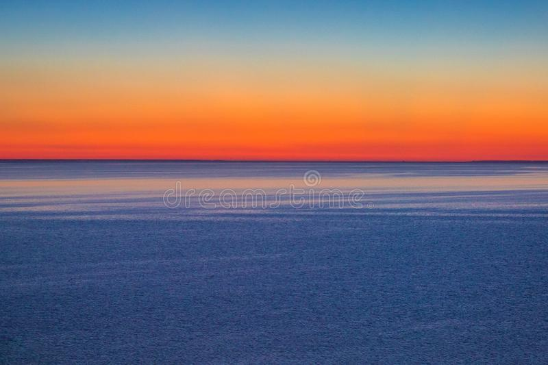 Red sunset sky on the water surface of the estuary royalty free stock photo