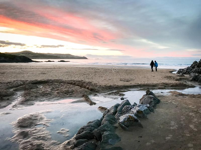 Red sunset walk along beach royalty free stock photos