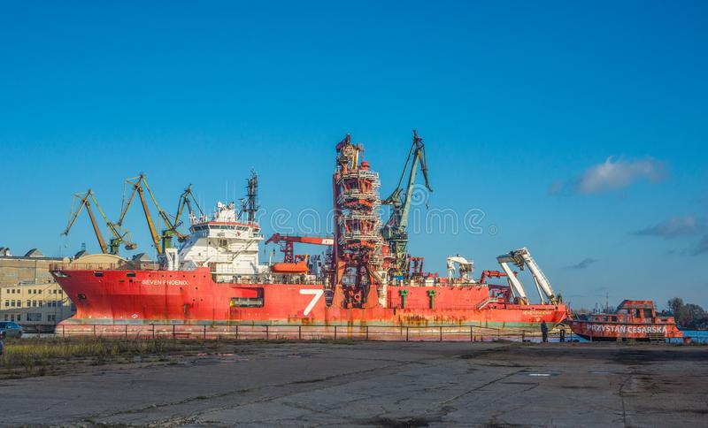 Red supply ship being reapired in a shipyard with scaffoldings stock photography