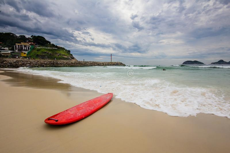 Red surfboard laying on shorebreak. In barra da tijuca beach royalty free stock images
