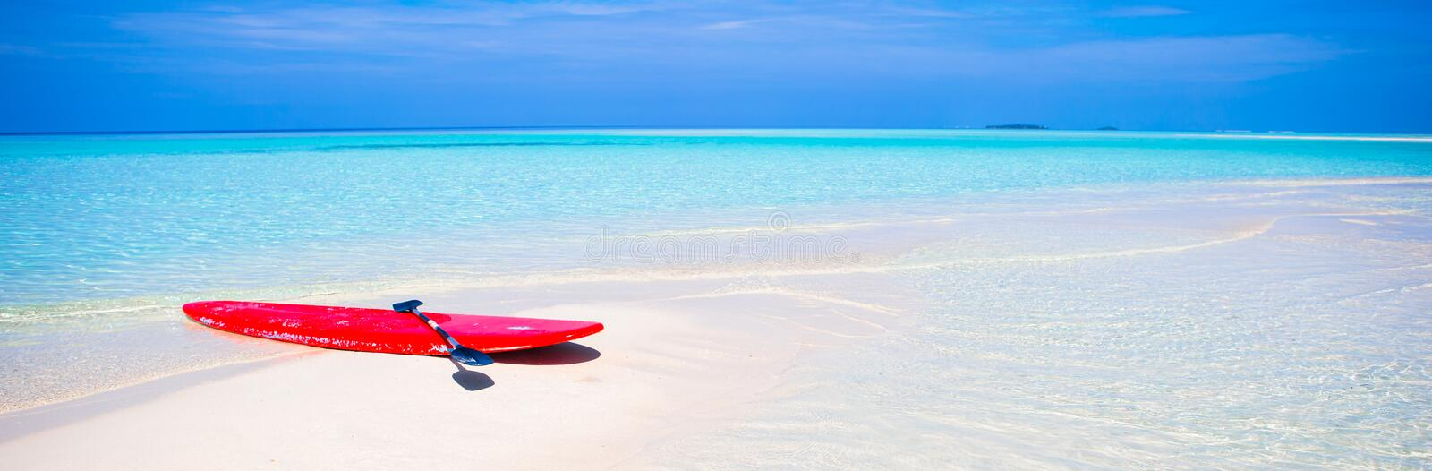 Red surfboard on white sandy beach with turquoise. Surfboard on white sandy beach with turquoise water royalty free stock image