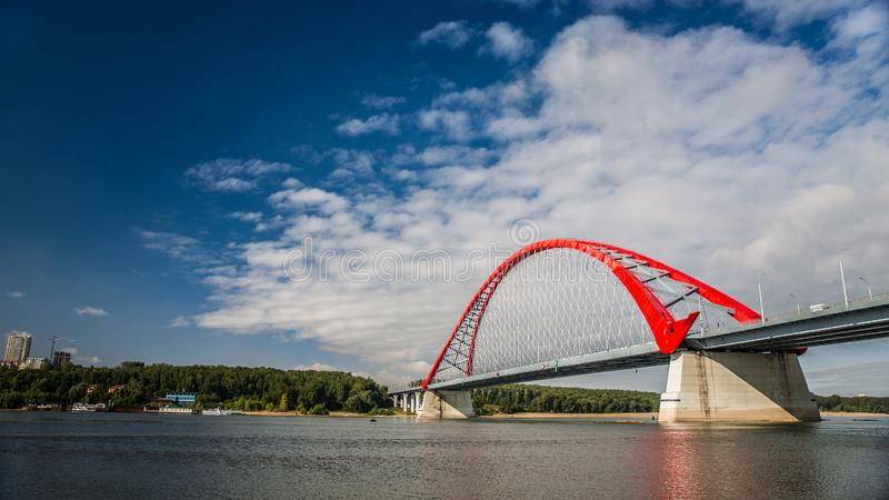 Red suspension bridge across the Ob River royalty free stock photo