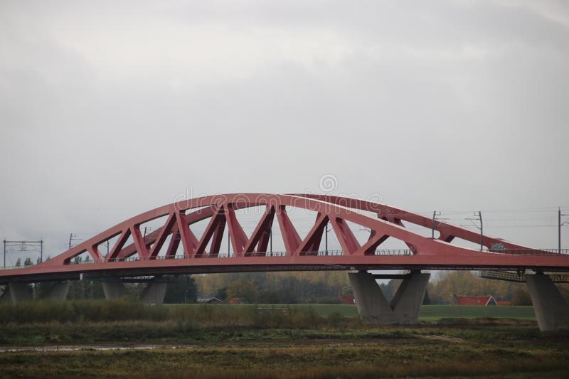 Red suspension bridge of steel over river IJssel at Zwolle in the Netherlands for trains. stock photo