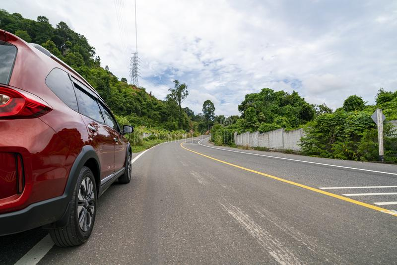 Red Suv car on Asphalt road with mountain green forest Transportation to travel concept royalty free stock photography