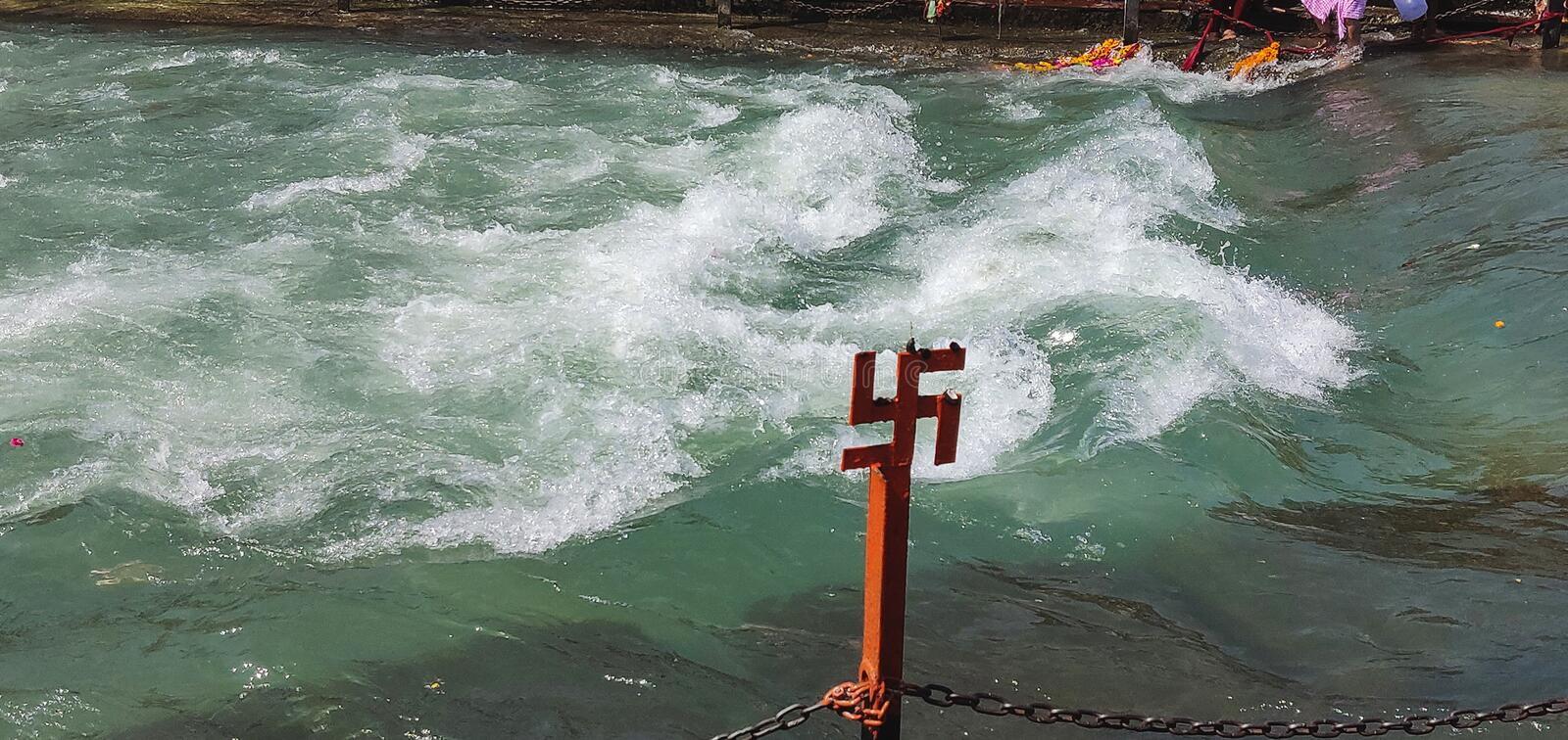 Red swastika cross on the Ganges River at Haridwar, India, sacred city for Hindu Religion. Pilgrims bathing on the ghats.  royalty free stock photos