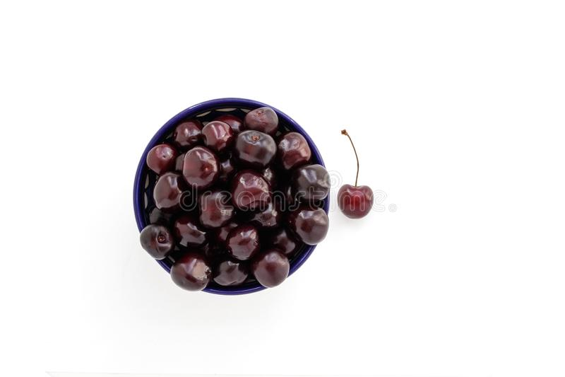 Red sweet cherry in a blue cup and one single berry on a white background royalty free stock image