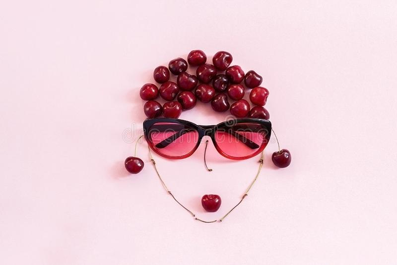 Red sweet cherry laid out in image of woman in sunglasses with lips on pink background. Concept youth, beauty, healthy eating or royalty free stock images