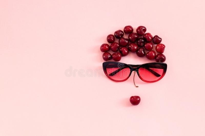 Red sweet cherry laid out in image of woman in sunglasses with lips on pink background. Concept youth, beauty, healthy stock image