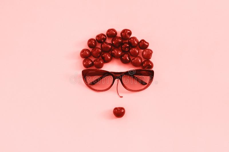 Red sweet cherry laid out in image of woman in sunglasses with lips on pink background, coral toned. Concept youth, beauty, royalty free stock photo