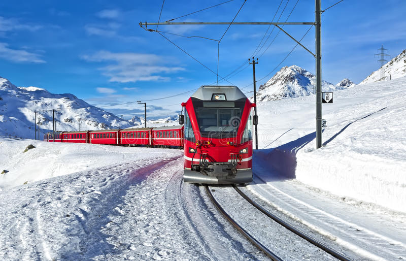 A red swiss train running through the snow. Switzerland royalty free stock image