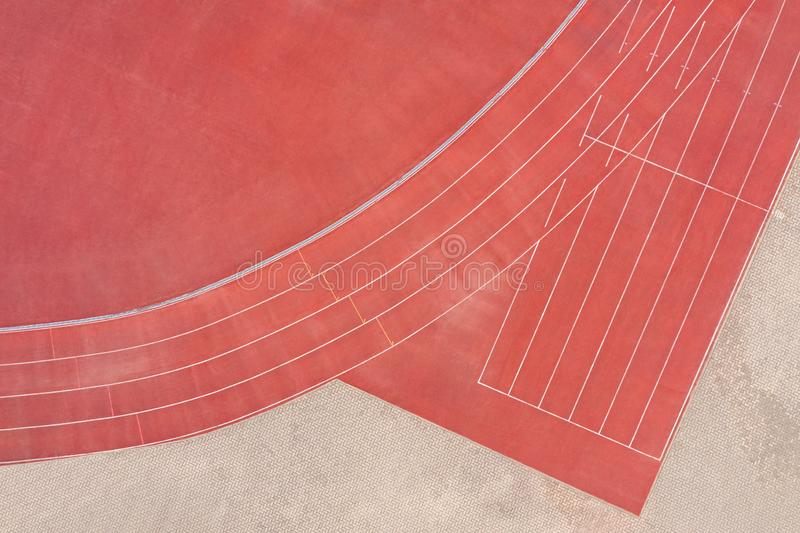 Red synthetic rubber athletic running track on stadium. aerial view royalty free stock photography