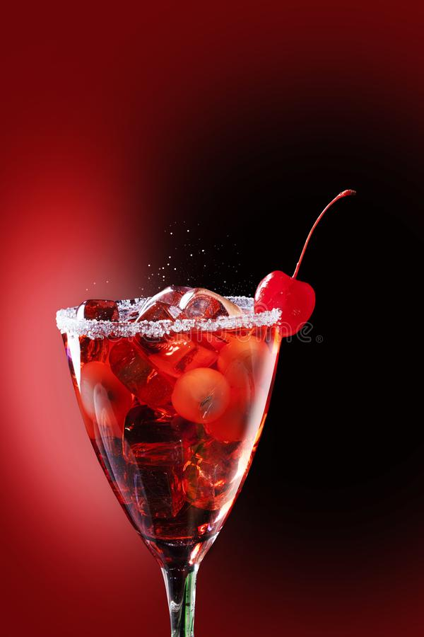 Red syrup. Tropical red cocktails with lychees and ice cubes, in a glass decorated with sugar and a cherry royalty free stock images