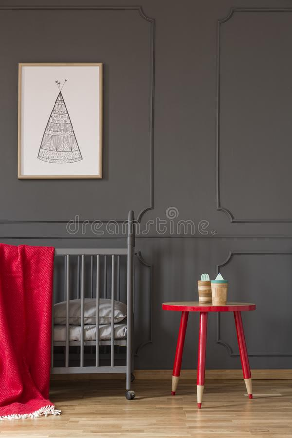 Red table next to cradle with blanket in kid`s bedroom interior. With poster on grey wall. Real photo concept stock photography