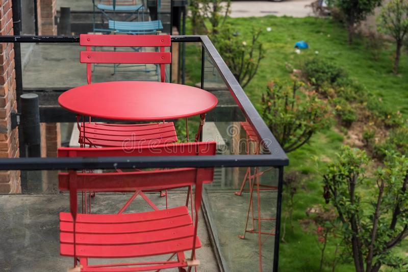 Red tables and chairs on the balcony. Closeup of red tables and chairs on the balcony of a hotel stock image