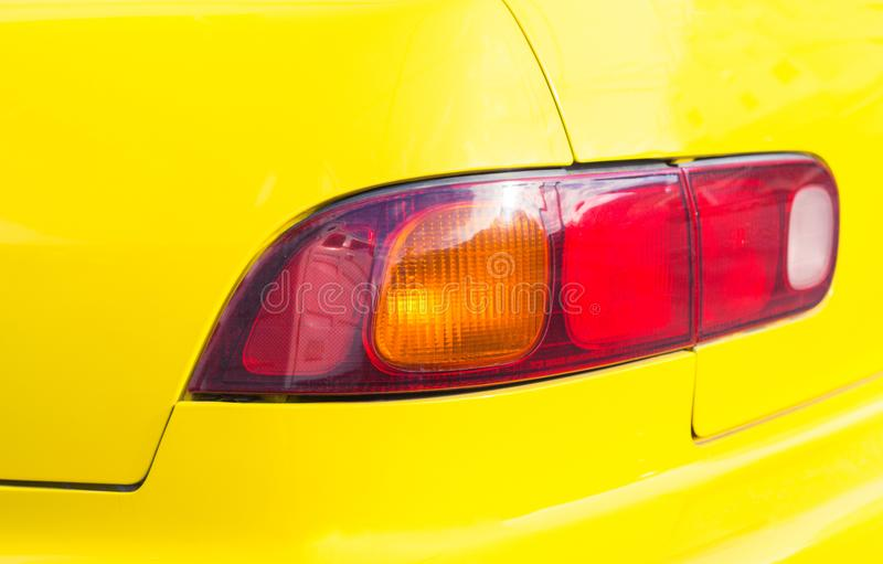 Red taillight on yellow car. Backlight of modern sport car. Four wheels transport. Shiny car detail closeup photo. Back lamp of yellow taxi cab. City transport stock image