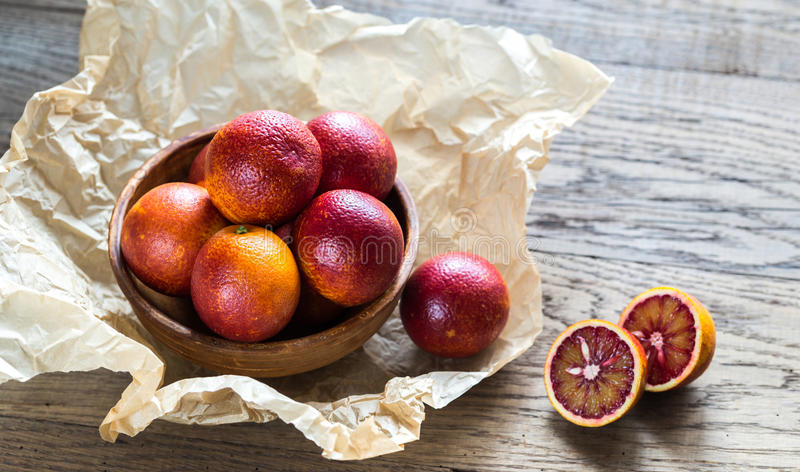 Red tangerines on the wooden background. Bowl of fresh red tangerines on the wooden background stock photography