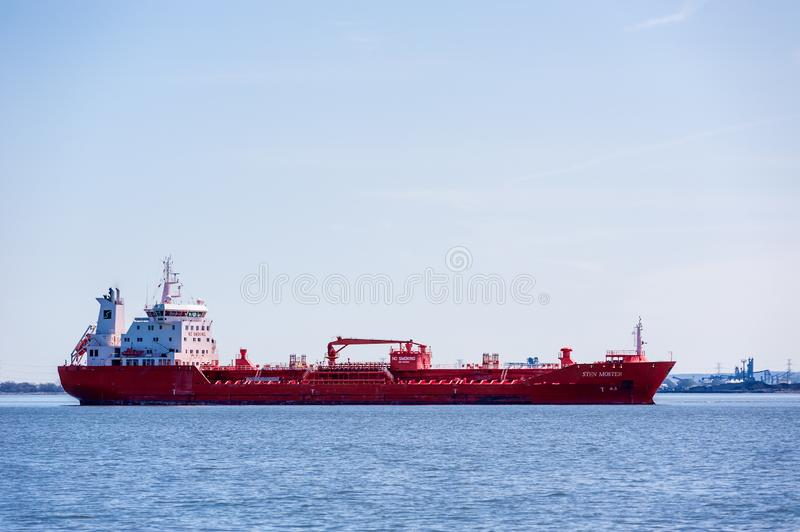 Red tanker ship anchored in bay near industrial area in Hamilton, Ontario, Canada royalty free stock photos