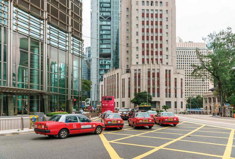 Red taxi cars are stuck in a traffic jam at Central District of Hong Kong city downtown. Taxi services are popular in Hong Kong royalty free stock images