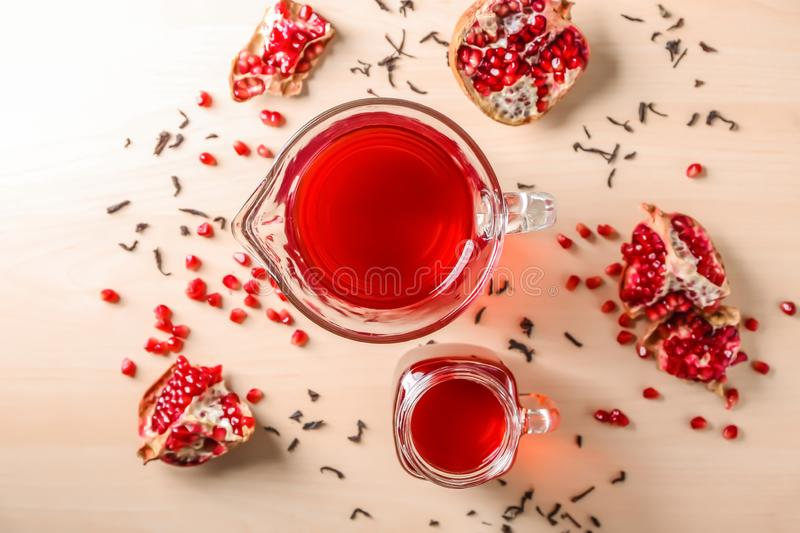 Red tea in mason jar and glass jug with pomegranate on light background, top view royalty free stock image