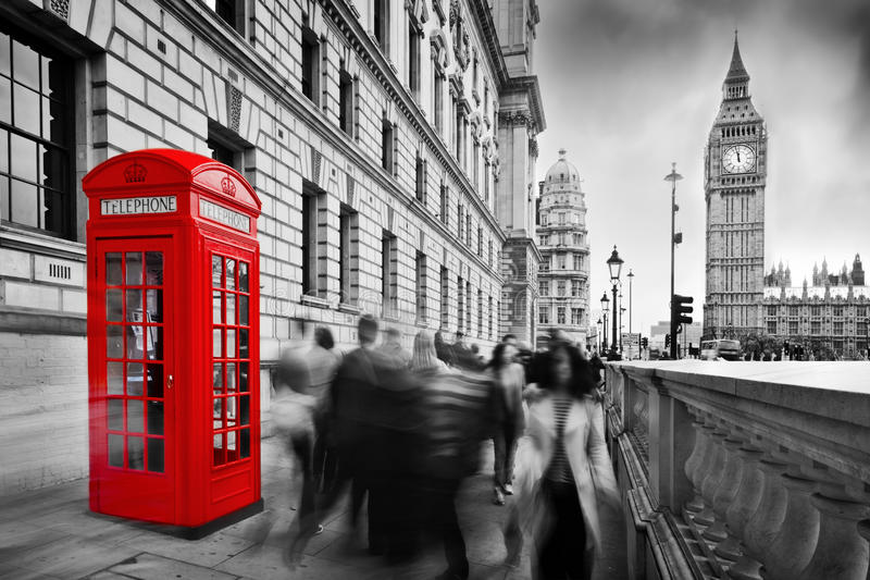 Red telephone booth and Big Ben. London, UK. Red telephone booth and Big Ben in London, England, the UK. People walking in rush. The symbols of London in black royalty free stock photos