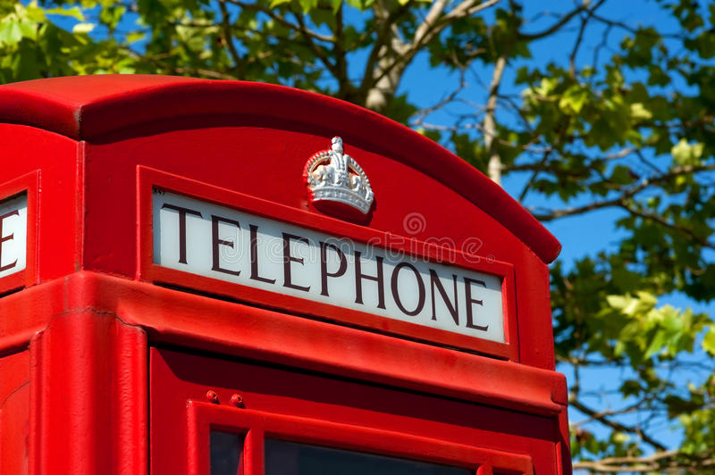 Red telephone box. Traditional british red telephone call box with a leafy background royalty free stock photography