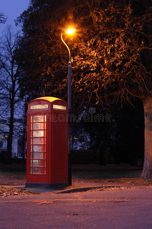Red Telephone Box. Bright red telephone box under an old style streetlight, taken early morning royalty free stock photo