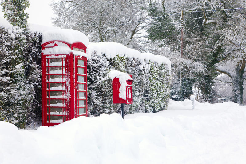Red telephone and post box in the snow royalty free stock photography