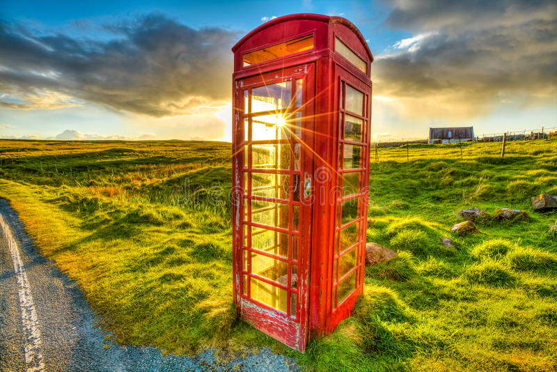 Red telephone. Urban red telephone box in the middle of a green countryside. Concept for synergy between modern city and rural area. The technology completes the