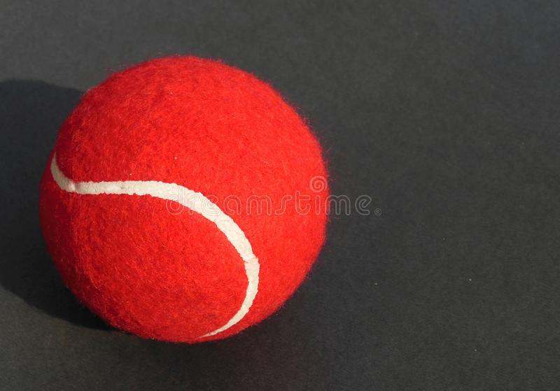 Red Tennis Ball with white curve line on dark grey background royalty free stock image