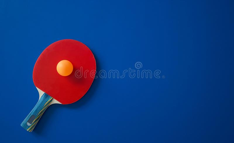 Red tennis racket lies on a blue table with a ball stock images