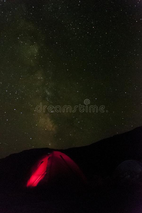 Red tent in mountains under the night sky filled with stars stock photo