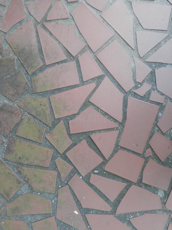 Red terracotta tile walkway background. Geometrically shaped abstract terracotta tiles, moss textured, fractured tile, grey grout stock photo