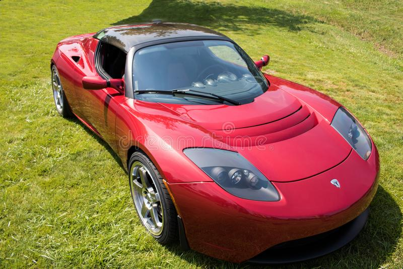 Red Tesla Roadster Sports Car Front Side in Green Field. Front side view of a bright red Tesla Roadster sports car parked in a green grassy field stock photos