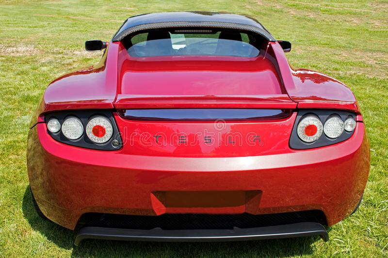 Red Tesla Roadster Sports Car Rear in Green Field. Rear view of a bright red Tesla Roadster sports car parked in a green grassy field stock photography