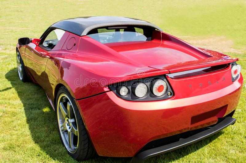 Red Tesla Roadster Sports Car Rear Side in Green Field. Rear side view of a bright red Tesla Roadster sports car parked in a green grassy field royalty free stock images