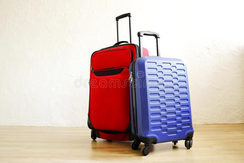 Red textile suitcase & blue hard shell luggage with extended telescopic handle up on wooden floor, white wall background. Couples stock images