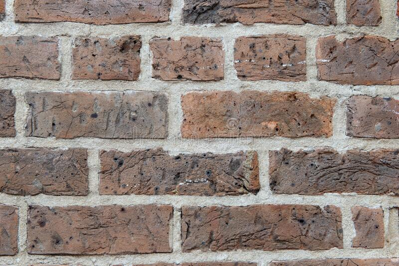 Red Textured Brick Wall with holes and paint. Red Old Textured Brick Wall with holes and paint close up in New Orleans, Louisiana stock photo