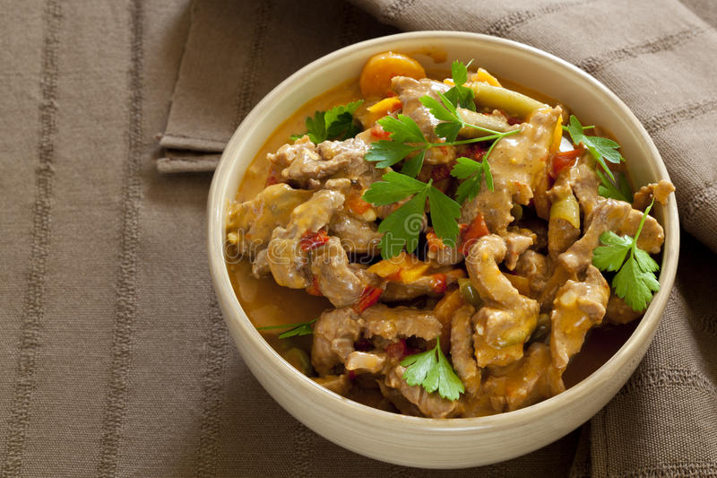 Red Thai Beef Curry. Bowl of red Thai beef curry, over brown linen stock photo