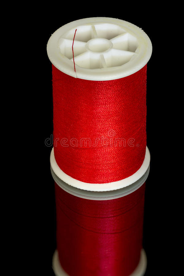 Red thread on a plastic spool for sewing royalty free stock image