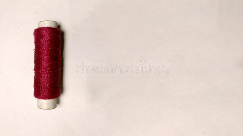 Red thread roll on white background royalty free stock image