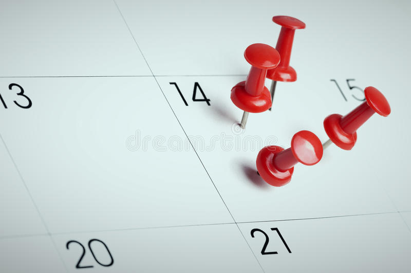 Red thumbtacks on calendar. Important date or meeting appointment reminder concept. Blue cast filter and copy space for text included stock photos