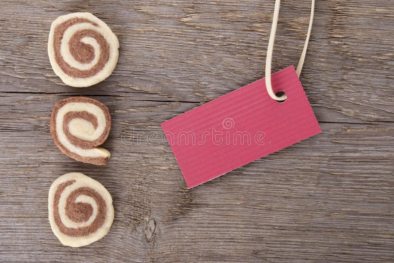 Red ticket with free space. A red sign with copy space and cookies on wood as background royalty free stock image