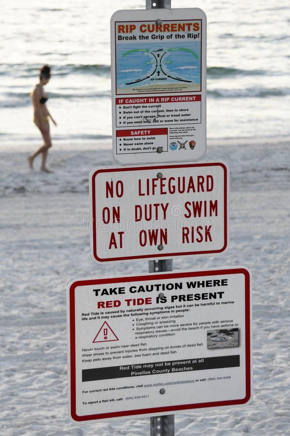 Red tide and rip current warning signs at St. Pete Beach, Florida. St. Pete Beach, Florida, October 24, 2018: Warning signs for red tide and rip currents are royalty free stock photo