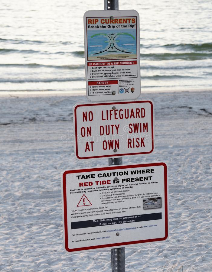 Red tide and rip current warning signs at St. Pete Beach, Florida. St. Pete Beach, Florida, October 24, 2018: Warning signs for red tide and rip currents are stock photography
