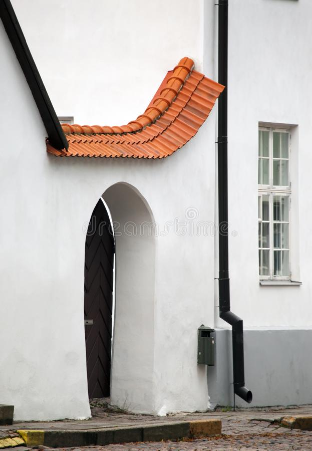 Red tile drain over a door in the white plastered wall of the medieval building, Tallinn royalty free stock photography