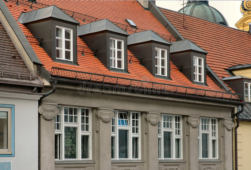 Red tile roof and gabled dormer windows in Munich, Germany royalty free stock photography